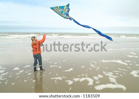 young girl flying a kite on the beach - stock photo