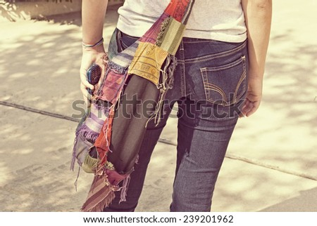 stock-photo-young-girl-from-the-back-in-jeans-holding-a-cell-phone-239201962.jpg