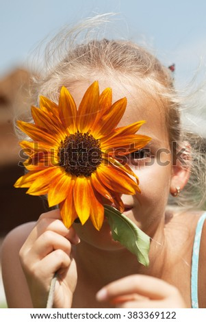 Young girl funny summer portrait with flower - closeup - stock photo