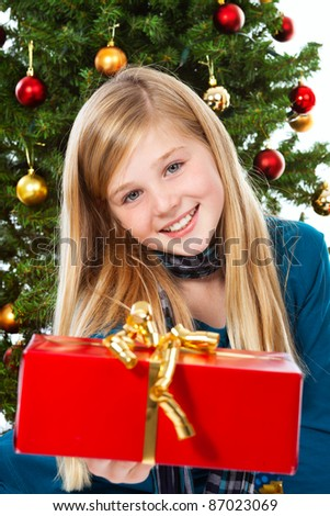 young girl giving a present, christmas tree in background