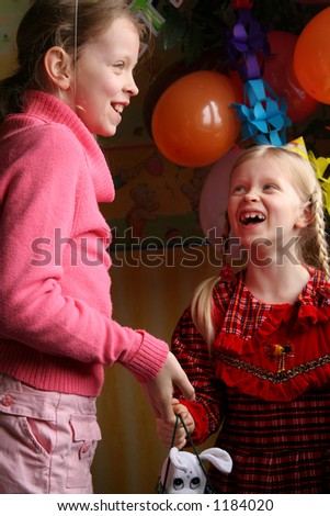 Young girl giving a present to a little girl - stock photo