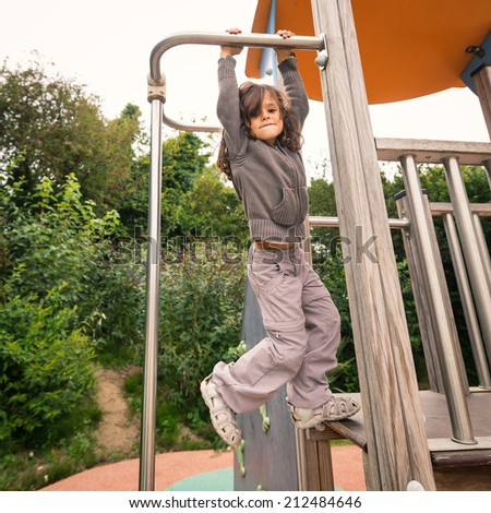 Young girl hanging up in a playground outdoor.  - stock photo