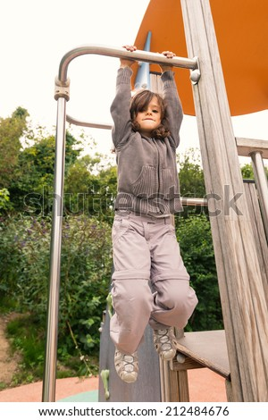 Young girl hanging up in a playground outdoor.