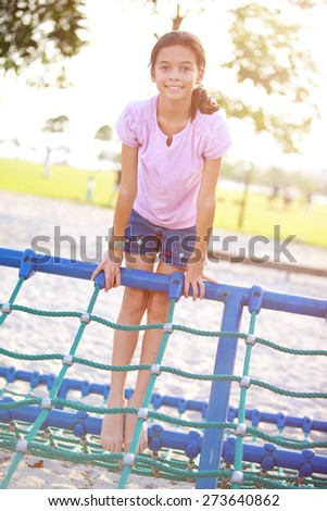 Young girl happily playing on climbing rope in park - stock photo