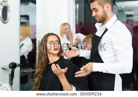 Young girl has a serious conversation with the hairdresser - stock photo
