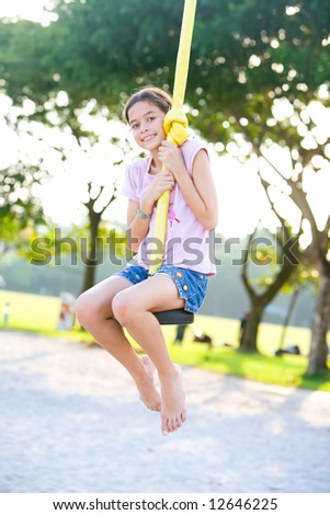 Young girl having fun playing on the swing at the playground - stock photo