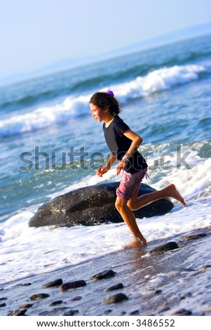 Young girl having fun running through the splashing waves by the sandy beach in a beautiful summer's afternoon.