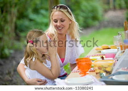 Young girl having fun with mom at the picnictable (shallow dof, focus on mother) - stock photo
