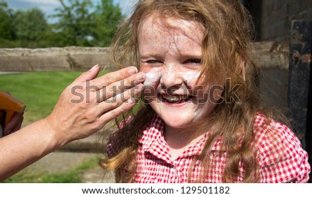 Young girl having her face covered with sun protection - stock photo