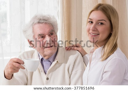 Young girl having teatime with her grandfather