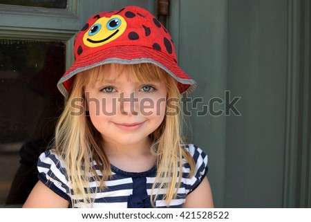 young girl headshot smiling against wall - stock photo