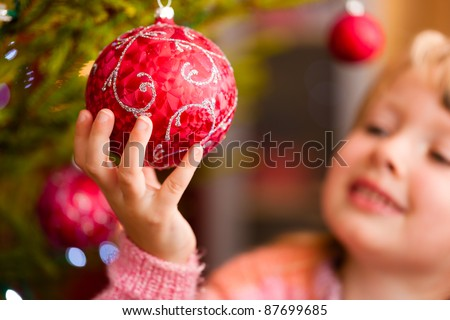 Young girl helping decorating the Christmas tree, holding some Christmas baubles in her hand - stock photo