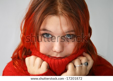 Young girl hides into the collar of the red sweater - stock photo