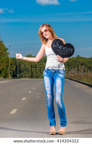 young girl hitchhiking on a country road - stock photo
