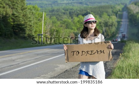 Young girl hitchhiking with placards in hand