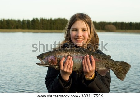 Young girl hold catched trout