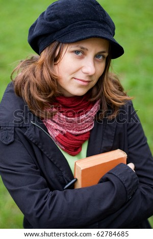 Young girl holding a book in her hands - stock photo
