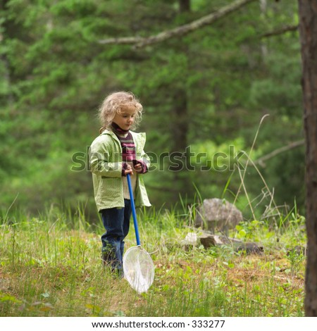 Young girl holding a butterfly net in the woods,