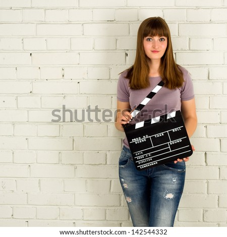 Young girl holding a clapboard. Brick wall with copy-space - stock photo
