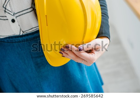 young girl holding a construction helmet