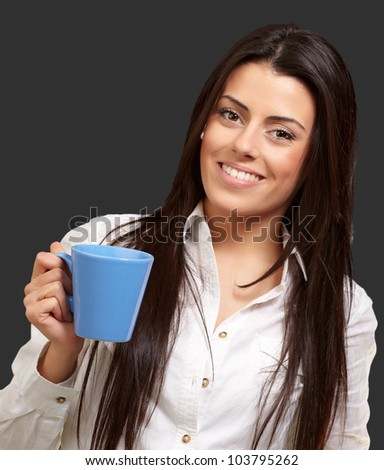 young girl holding a cup over a black background