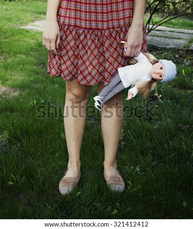 Young girl holding a doll. Leaving childhood - stock photo