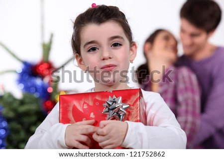 Young girl holding a gift on Christmas Day - stock photo
