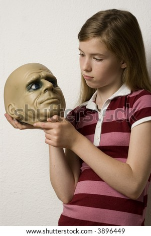 Young girl holding a halloween head