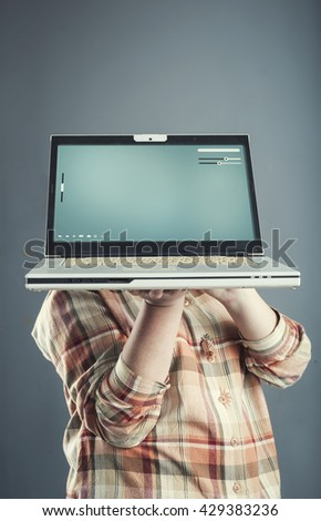 Young girl holding a laptop in front of her head - stock photo