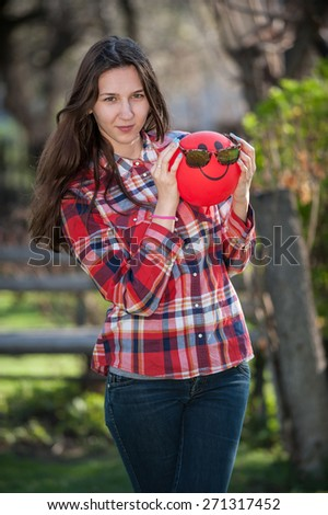 Young girl holding a red balloon looking at the camera vertical - stock photo