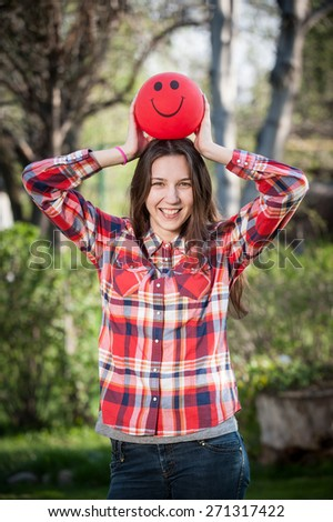 Young girl holding a red balloon over her head - stock photo