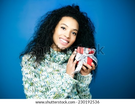 Young girl holding a small present and smiling - stock photo