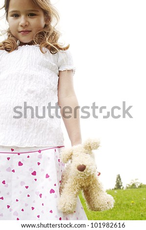 Young girl holding a soft toy in the park, looking at camera. - stock photo