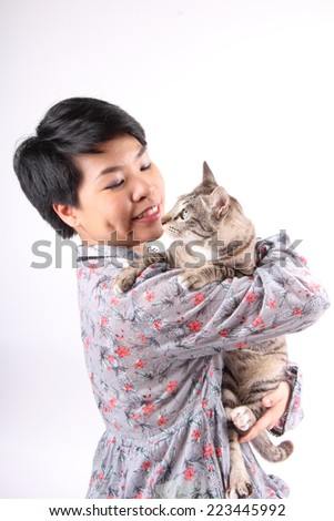 Young girl holding a tabby cat