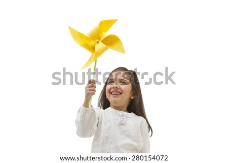 Young girl holding a toy windmill - stock photo