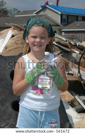 Young girl holding a water bottle in front of some rubble removed from her house. Roofing crew in the background. - stock photo