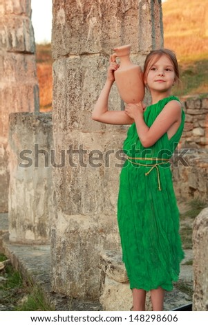 Young girl holding an ancient amphora on the excavation of the ancient city Pantikapaion - stock photo