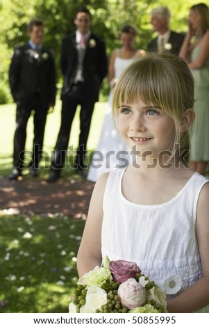 Young girl holding bouquet, bride and groom in background