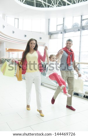 Young girl holding hands and swinging between mother and father - stock photo