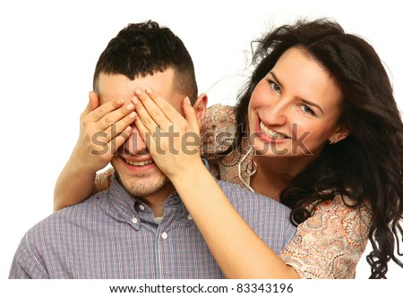 Young girl holding hands on eyes of her boyfriend isolated on white - stock photo
