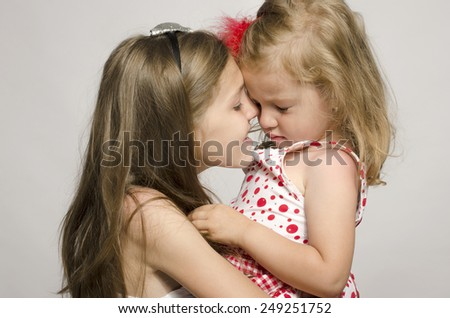 Young girl holding in her arms and kissing and having fun with her small sister. Girl trying to make her small upset sister smile  - stock photo
