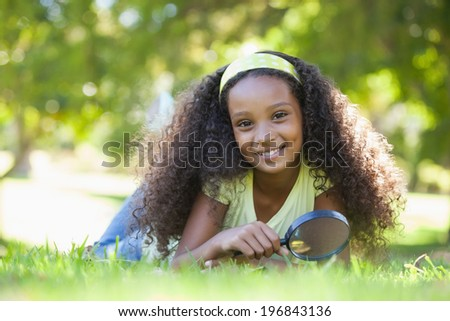 Young girl holding magnifying glass in the park smiling at camera on a sunny day - stock photo