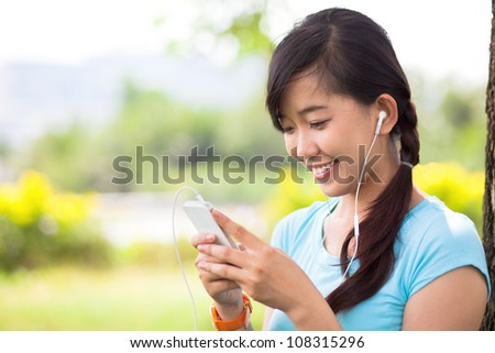 Young girl holding mp3 player in earphones on top of her head and listening music - stock photo
