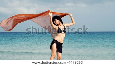 Young girl holding orange cloth in ocean background