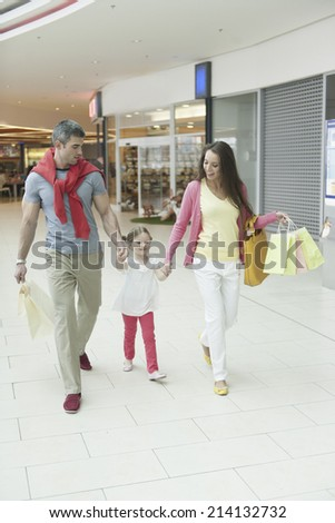 Young girl holding parents hands in shopping mall - stock photo