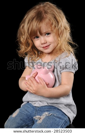 Young girl holding piggy bank isolated over a black background - stock photo