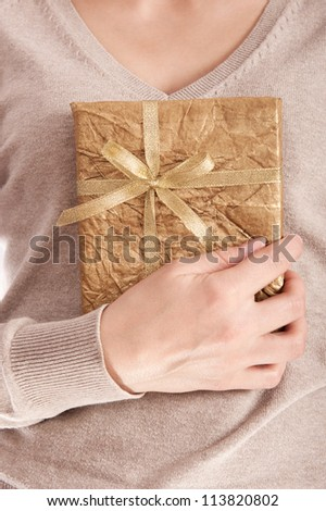 Young girl holding present box with ribbon bow
