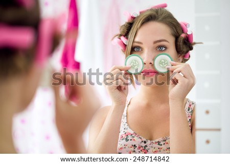 Young girl holding slice cucumber for eyes treatment front mirror - stock photo