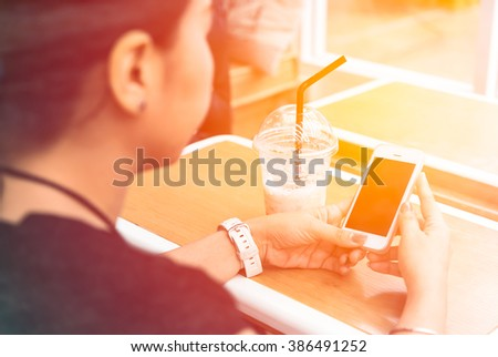 Young girl holding smart phone and drinking coffee inside coffee shop (pastel filter) - stock photo