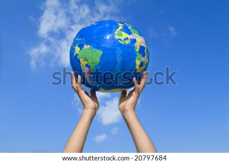 young girl holding the earth in her hands (blue sky)